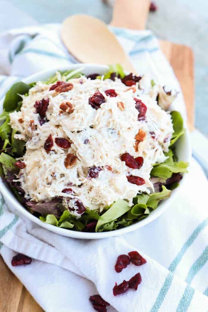 Apple Pecan Greek Yogurt Chicken Salad in a while bowl on a green towel