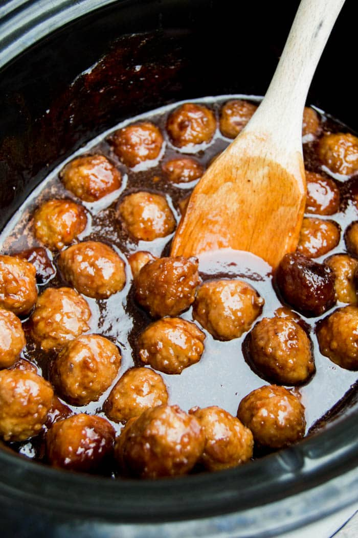 3 Ingredients Meatballs in a slow cooker with a wooden spoon