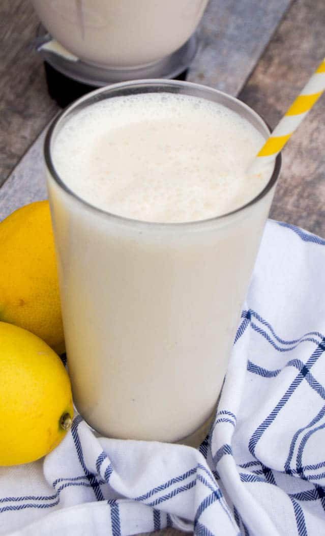 Closeup of frosted lemonade on a white and blue towel with lemons