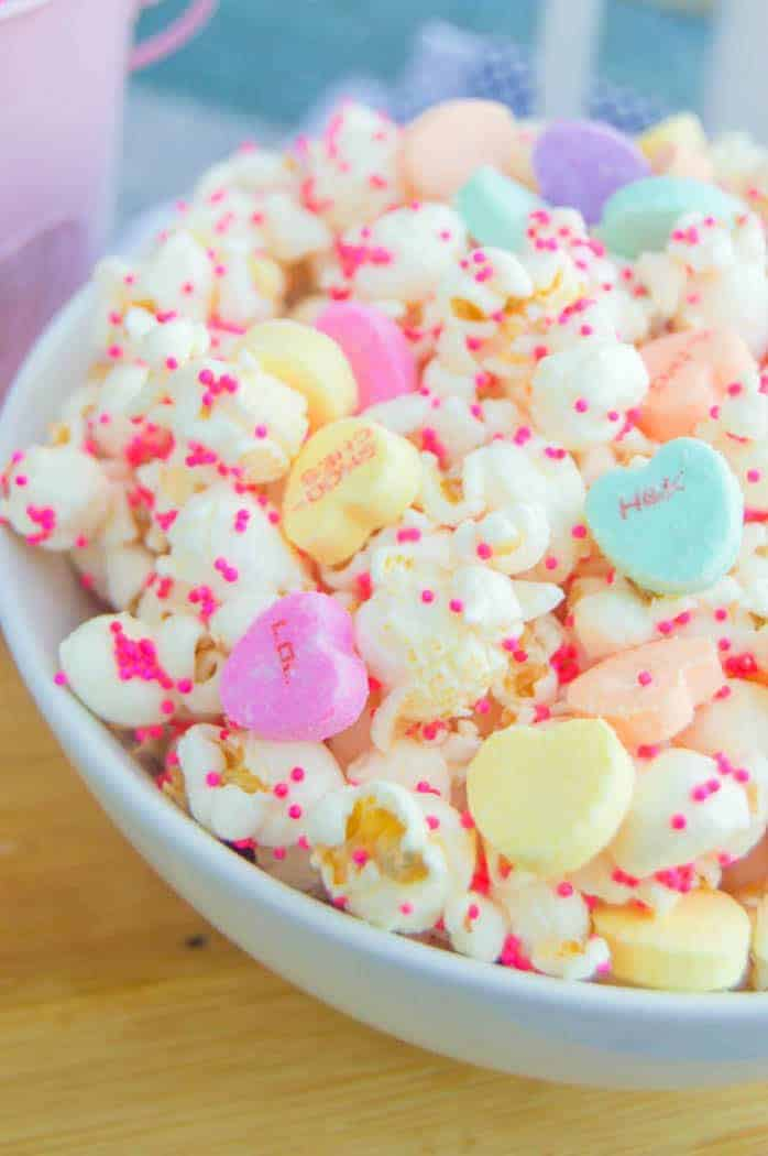 Closeup shot of Valentine's Day Popcorn with heart candies and sprinkles in a white bowl
