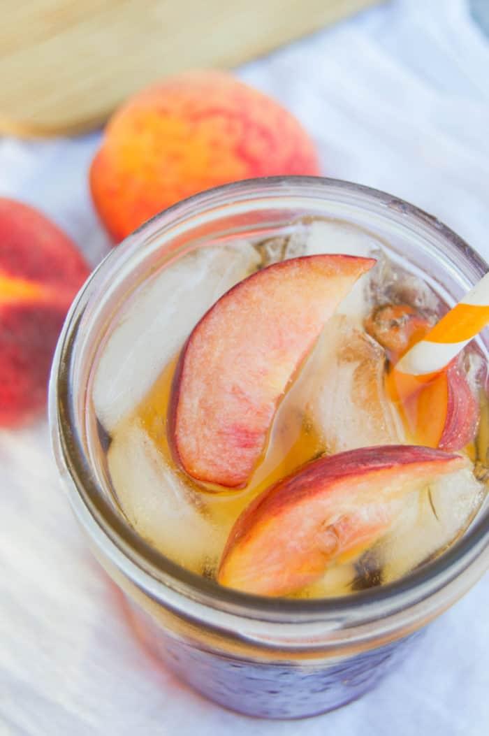 Peach Sweet Tea close up in mason jar with peaches behind it