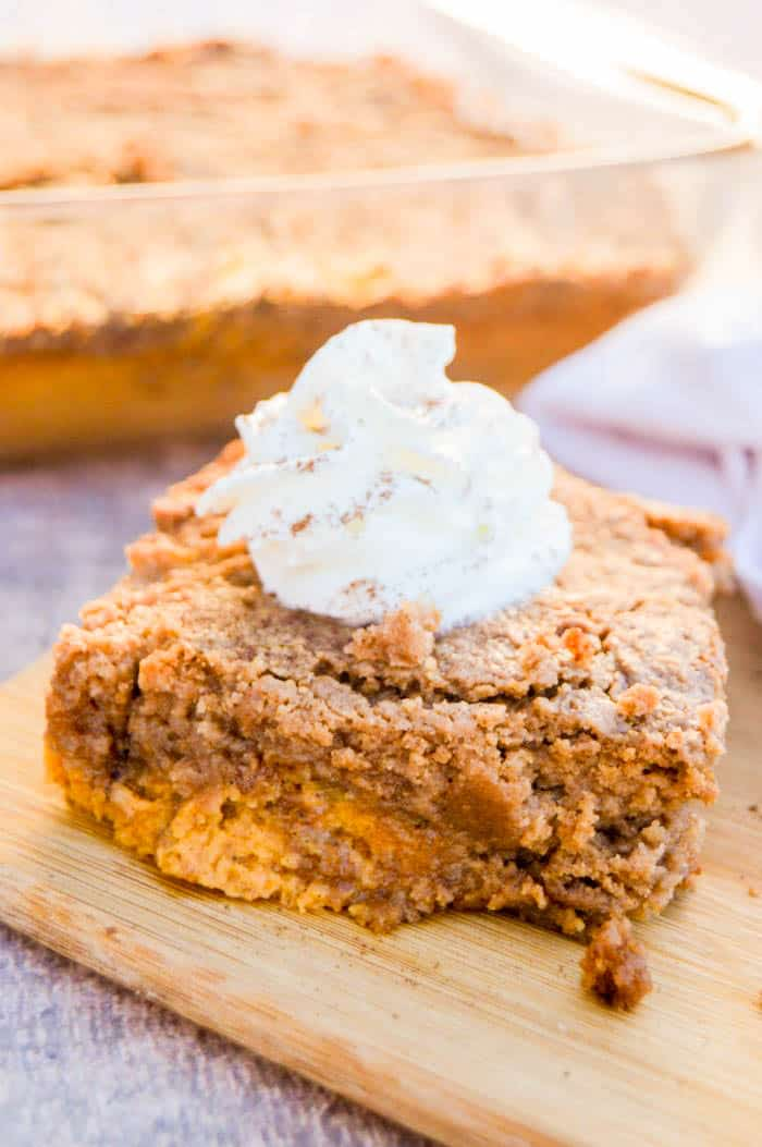 Pumpkin Spice Dump Cake on a cutting board with whipped cream