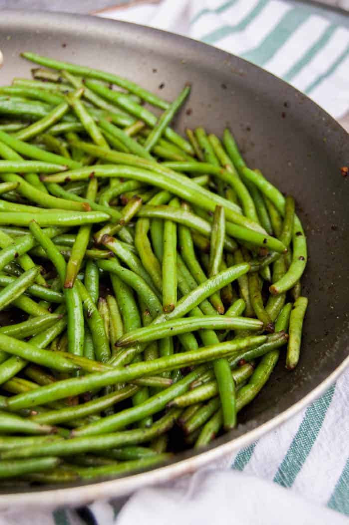 Closeup shot of green beans in skillet on white and green cloth