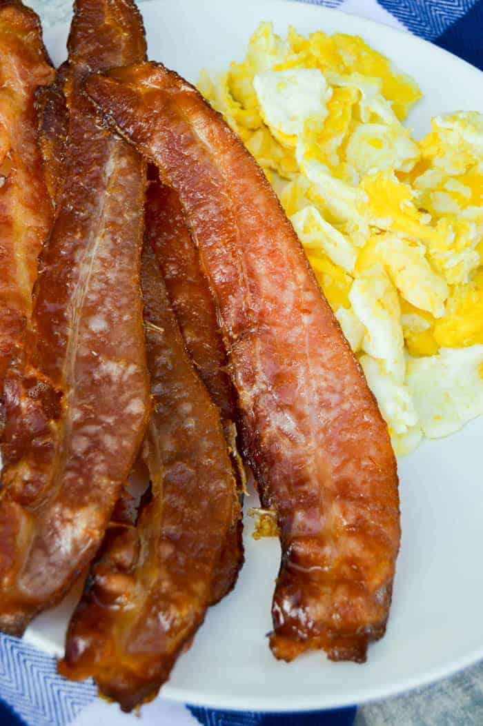 Oven Baked Bacon on white plate with scrambled eggs