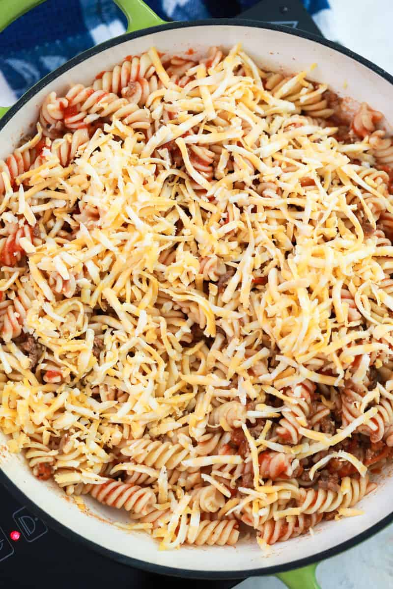 topping the cheesy taco pasta with shredded cheese