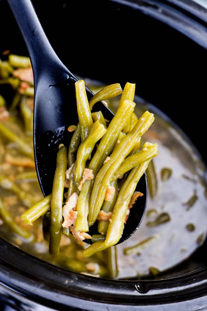 Slow Cooker green beans out of the crockpot on a black spoon