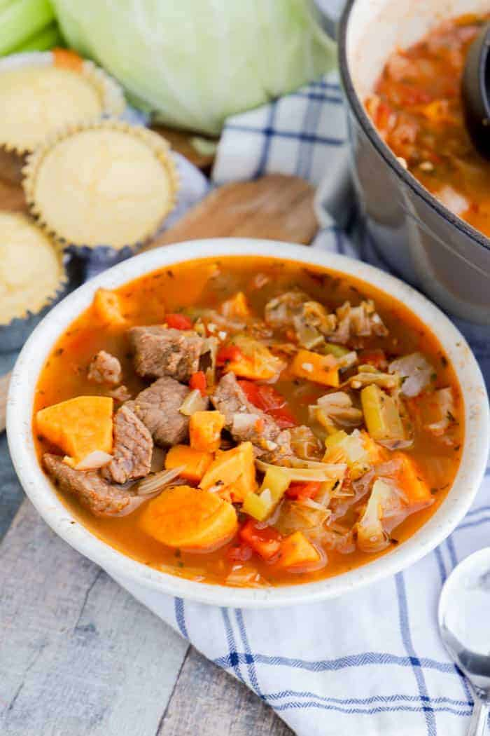 Sweet Potato Beef Stew in a white bowl with cornbread