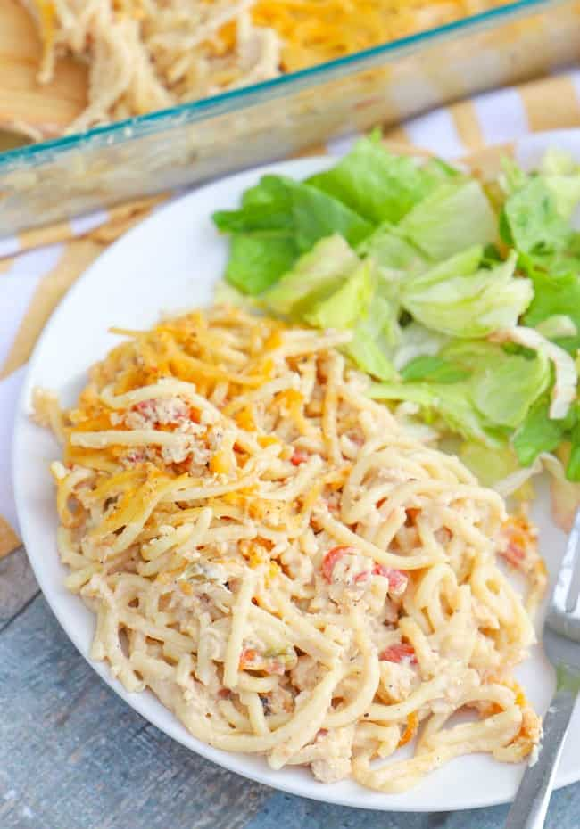 Chicken Spaghetti Casserole on a white plate with salad.
