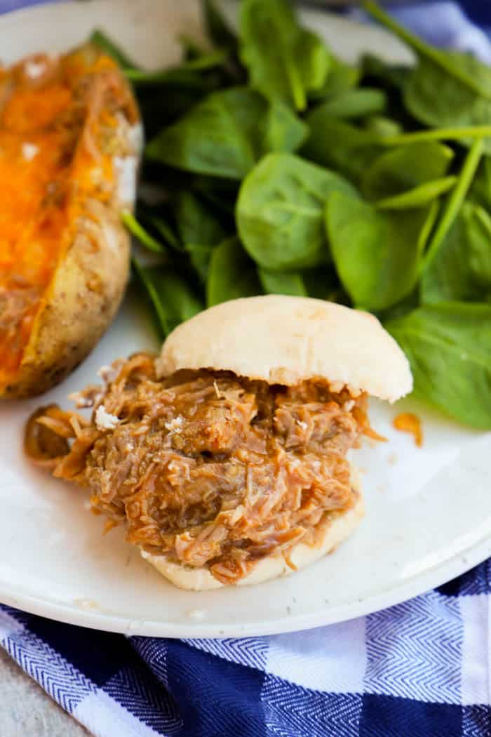 Slow Cooker Pulled Pork Sliders on a plate with salad and baked potato