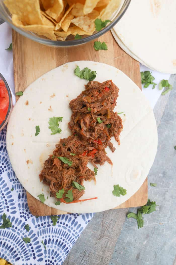 4 Ingredient Slow Cooker Steak Fajita on the table with chips and tomatoes