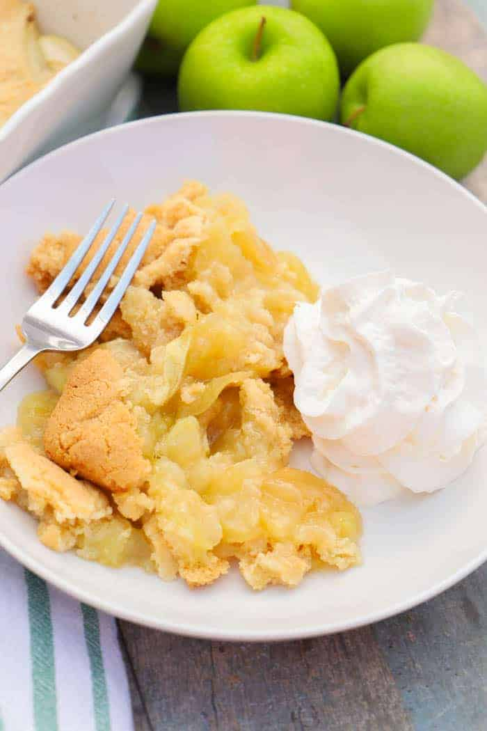 Apple Cobbler in a white plate with whipped cream