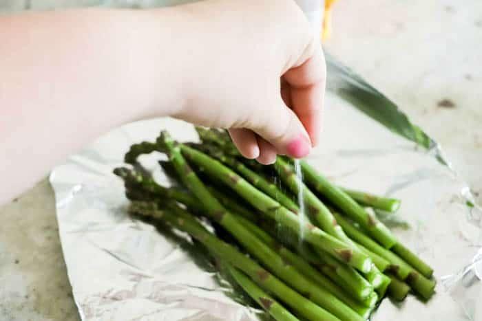 sprinkling salt on Grilled Asparagus
