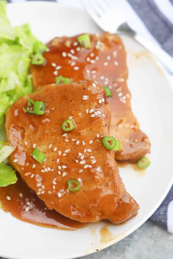 Teriyaki Pork Chops on a plate with sesame seeds and green onions