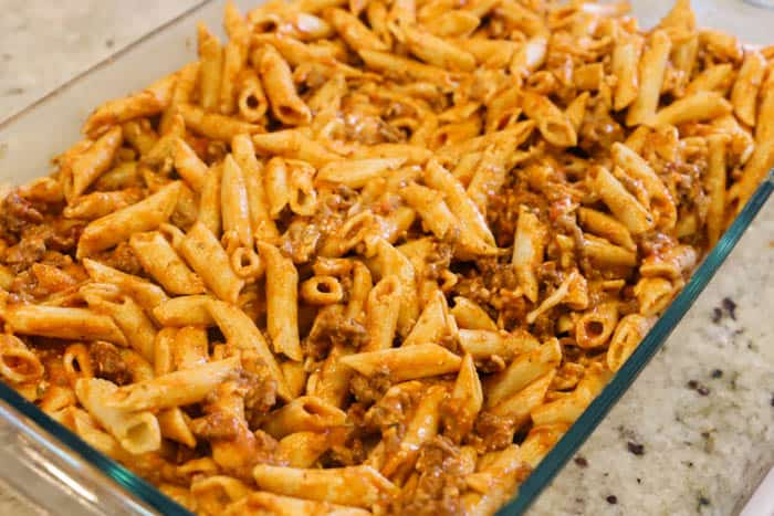 adding pasta to a casserole dish to bake