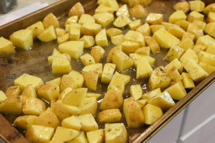 adding potatoes to the sheet pan