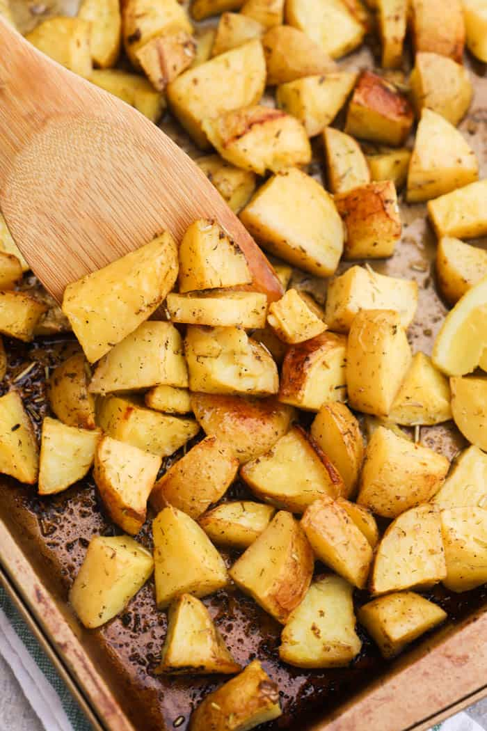 Lemon Herb Roasted Potatoes on a pan with a wooden spoon