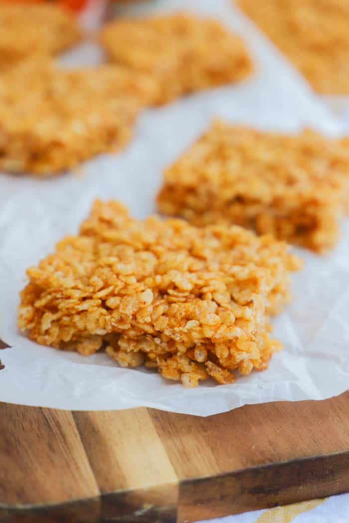 Pumpkin Spice Rice Krispies Treats on a brown cutting board