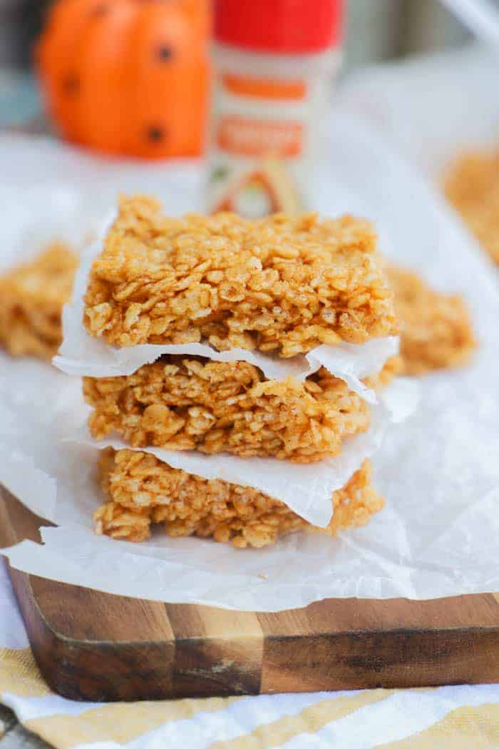 Pumpkin Spice Rice Krispies Treats stacked on a cutting board