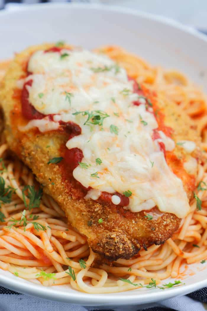 Baked Chicken Parmesan on top of spaghetti