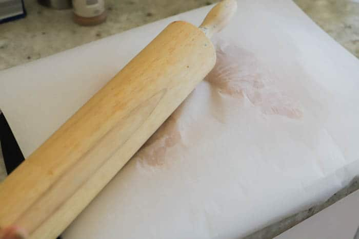 using rolling pin on chicken to flatten