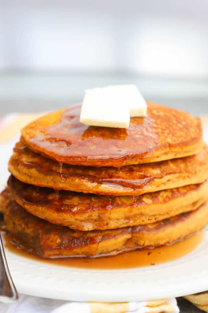 Pumpkin Pancakes stacked on a white plate with butter