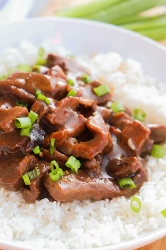 Slow Cooker Mongolian Beef in a white bowl on rice