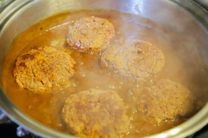 adding patties back into the pan with gravy