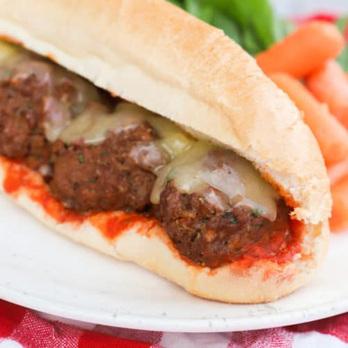 Meatball Subs on a white plate with salad and carrots