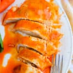 Baked Buffalo Chicken on a white plate cut up to serve