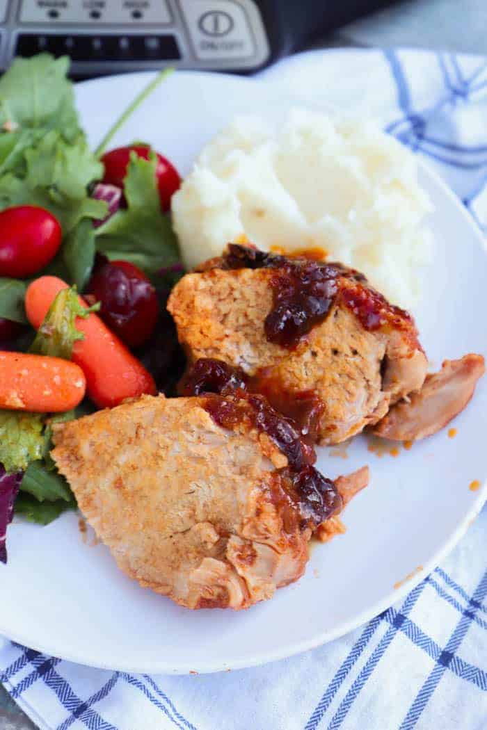 Slow Cooker Cranberry Pork Loin on a plate with salad and mashed potatoes