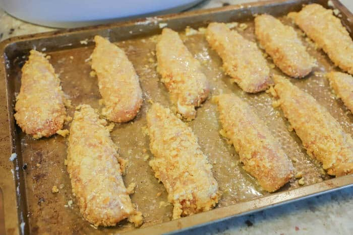 uncooked and breaded chicken on a baking sheet