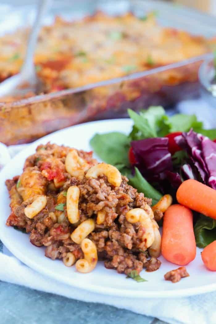 Chili Mac Casserole on a plate with a salad and carrots