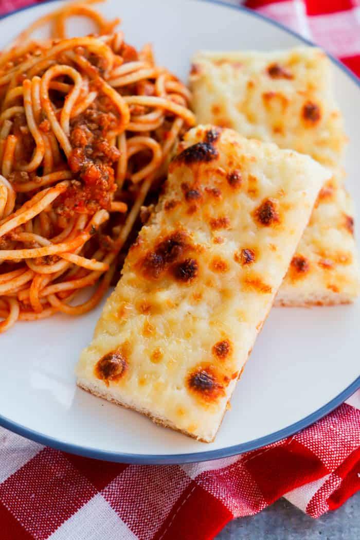 Garlic Flat Bread Sticks on a plate with spaghetti