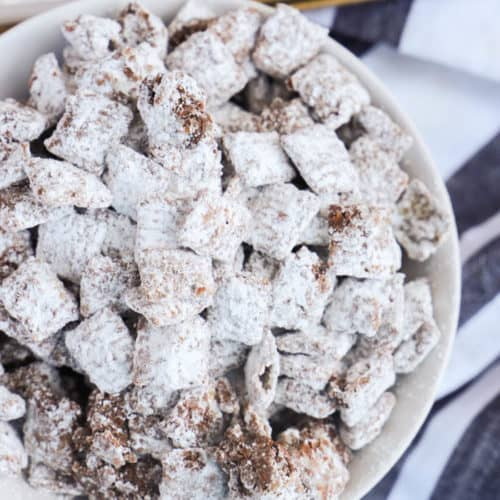 Muddy Buddies in a white bowl and black napkin