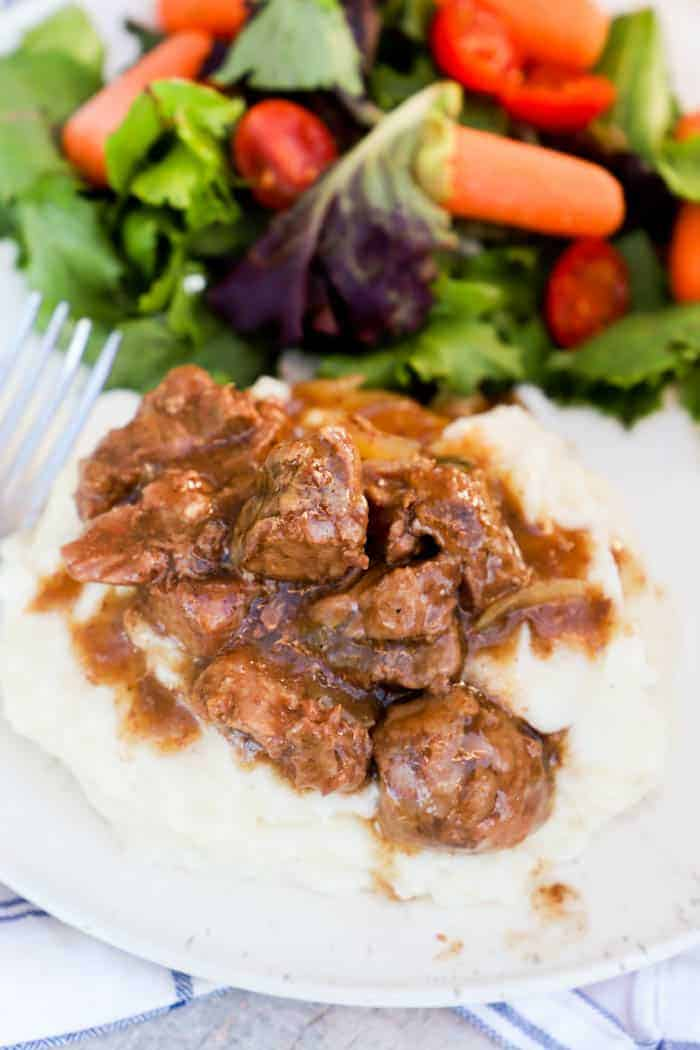 Slow Cooker Beef Tips on a white plate on mashed potatoes