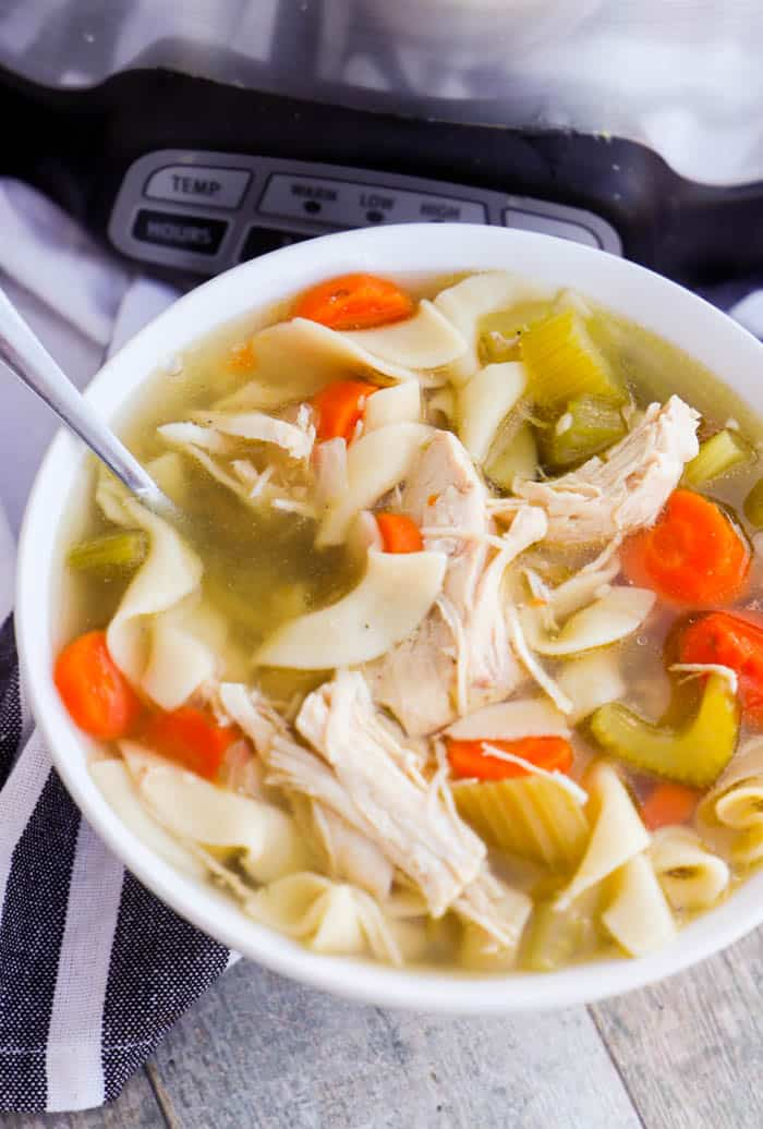 Slow Cooker Chicken Noodle Soupm in awhite bowl with a spoon