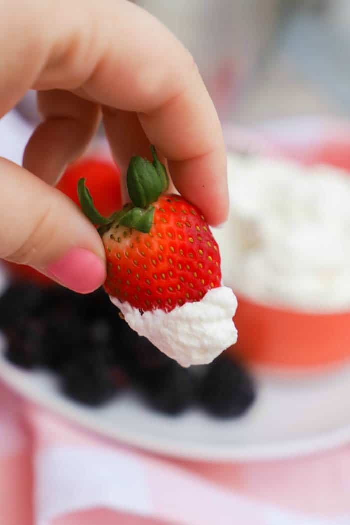 Homemade Whipped Cream on a fresh strawberry