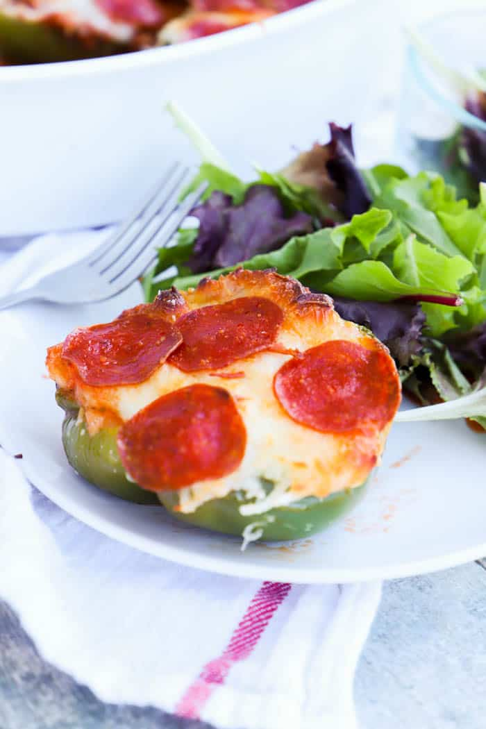 Pizza Stuffed Peppers on a white plate with salad
