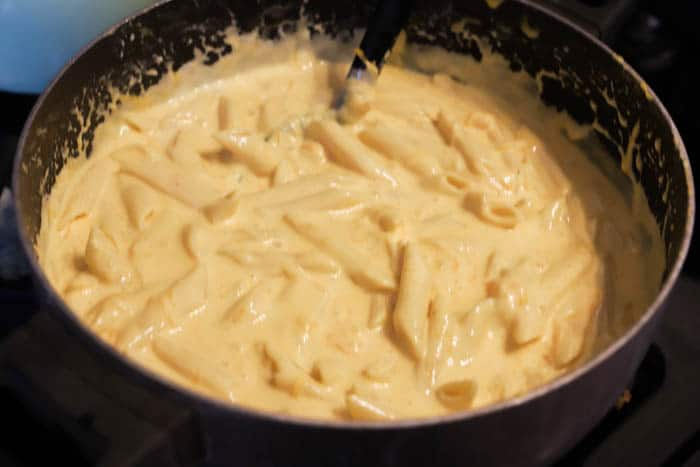 Cheesy Penne Bake in a sauce pan melting cheese