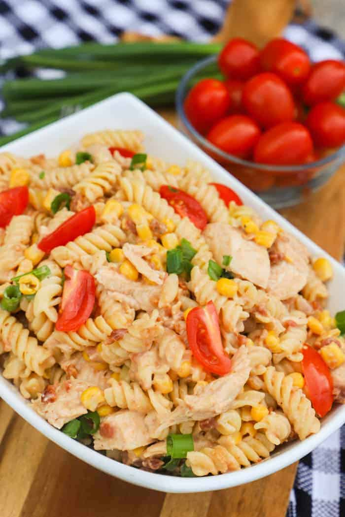 BBQ Chicken Pasta Salad in a white bowl with side of tomatoes