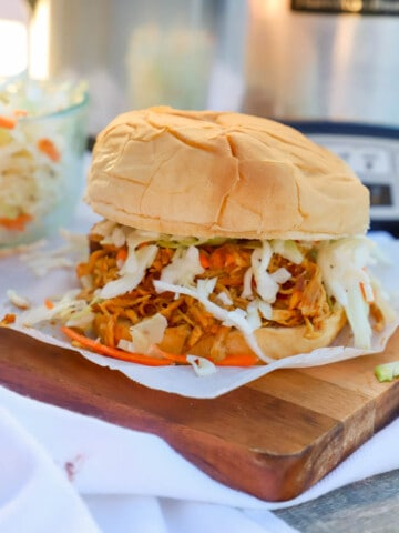 Slow Cooker Shredded Asian Chicken Sandwich on a wooden serving dish