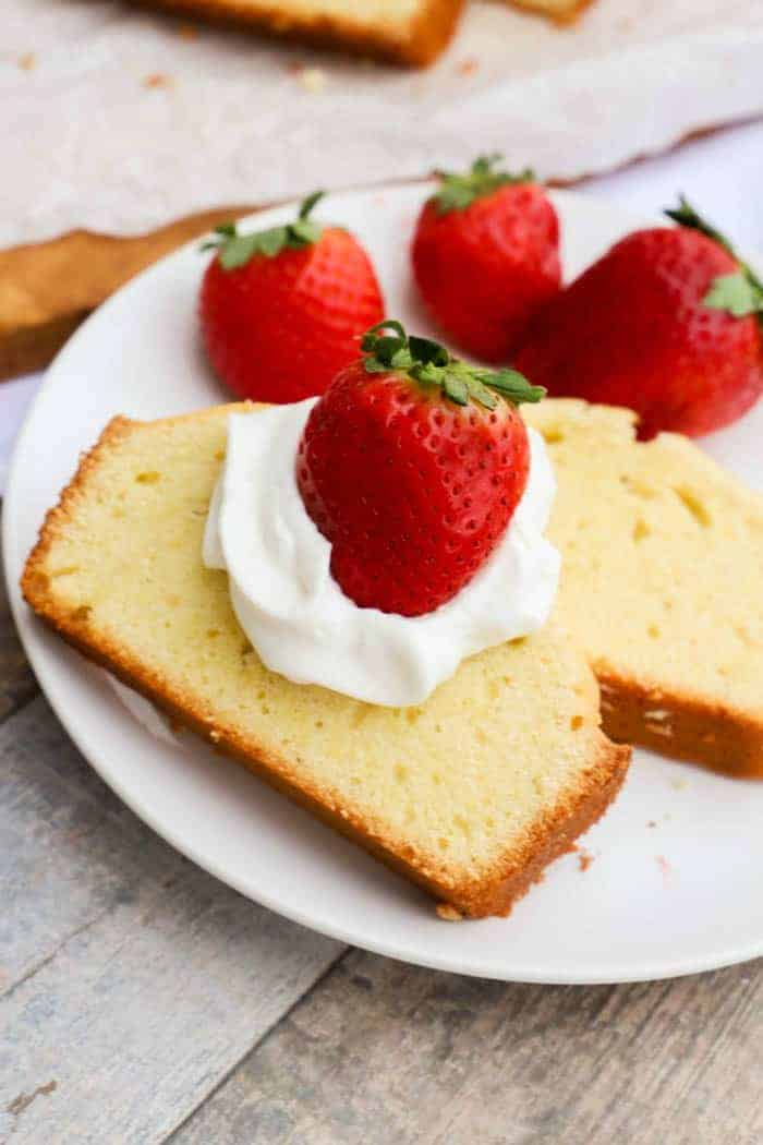 Million Dollar Pound Cake with whipped cream and strawberries