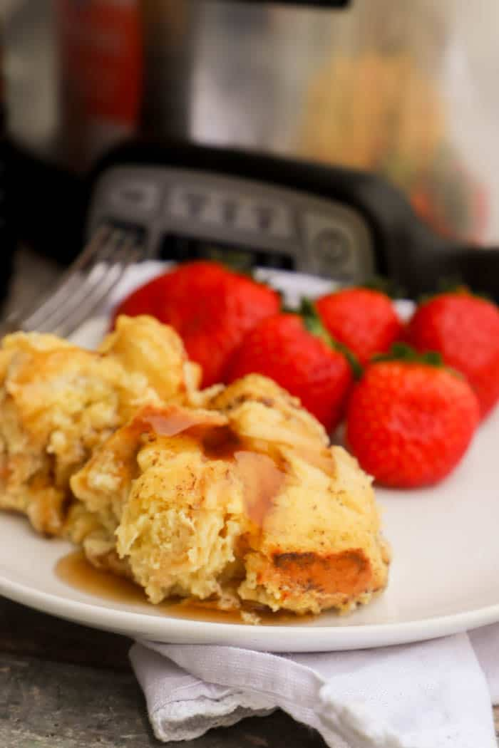 Slow Cooker French Toast Casserole on a white plate with strawberries