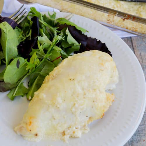 Baked Creamy Swiss Chicken on a plate with a salad