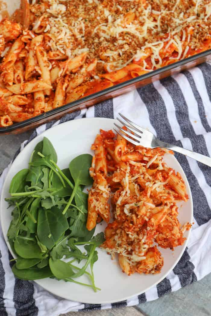Chicken Parmesan Casserole on a white plate with salad