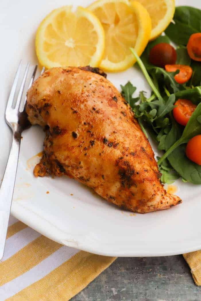 chicken marinade on a plate with salad and slice lemons