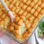 tater tot casserole in a casserole dish with pink spoon