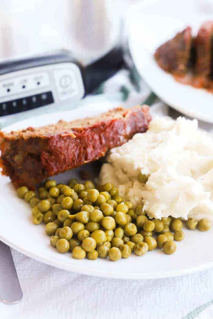 Slow Cooker Meatloaf on a plate with peas and mashed potatoes