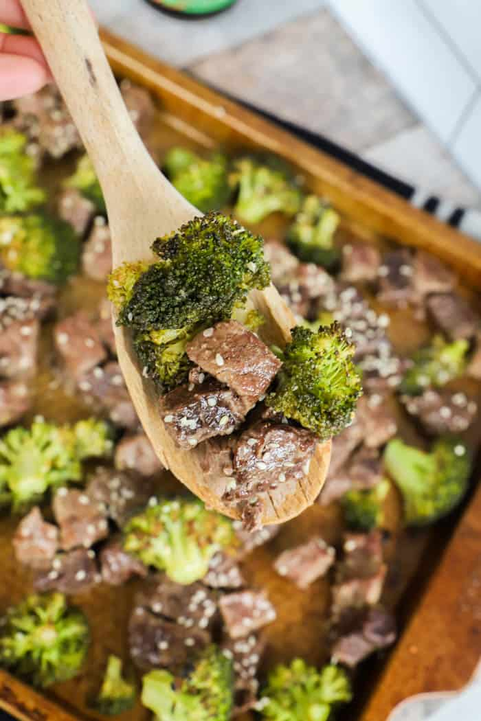 Sheet Pan Beef and Broccoli on a wooden spoon