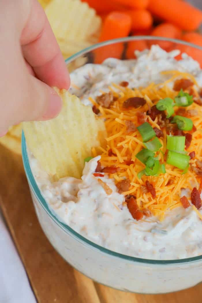 Loaded Ranch Dip dipping with a chip